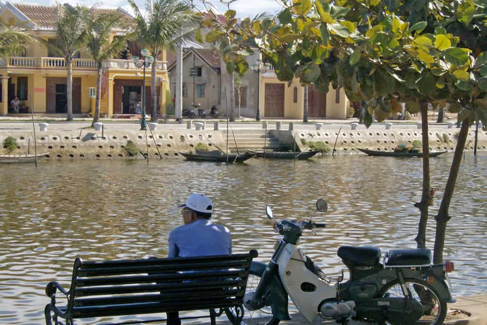 Man sits on a bench beside a motorbike near a river