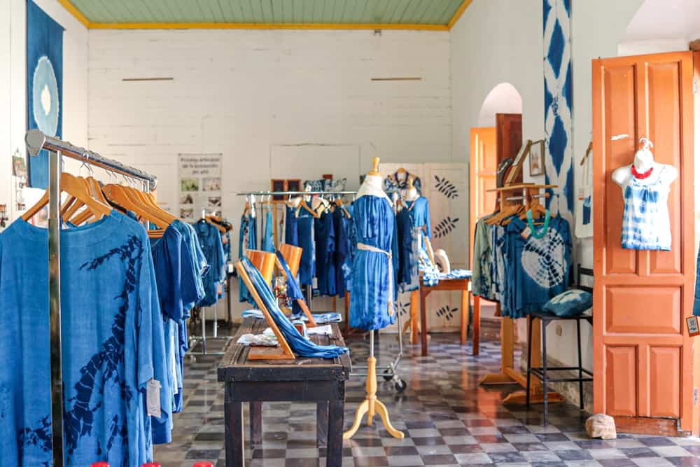 Many blue clothes hanging in a shop