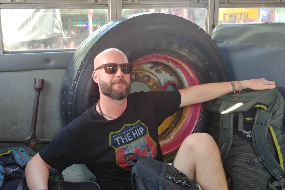 Man sitting on the floor of a bus beside a tire