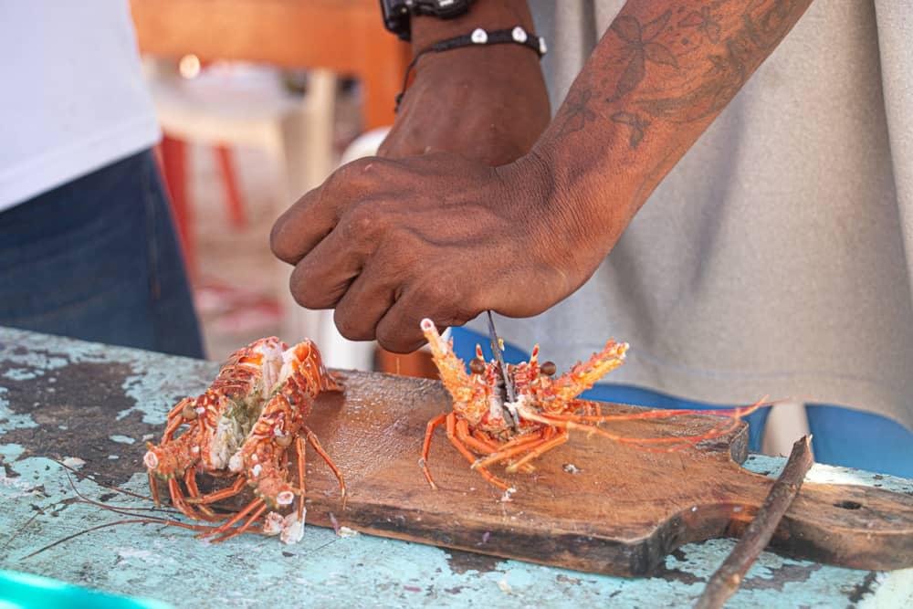 Man cuts lobster on a cutting board
