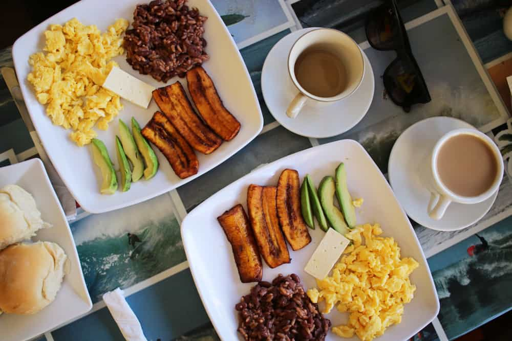 Two plates with breakfast items and two cups of coffee in El Salvador