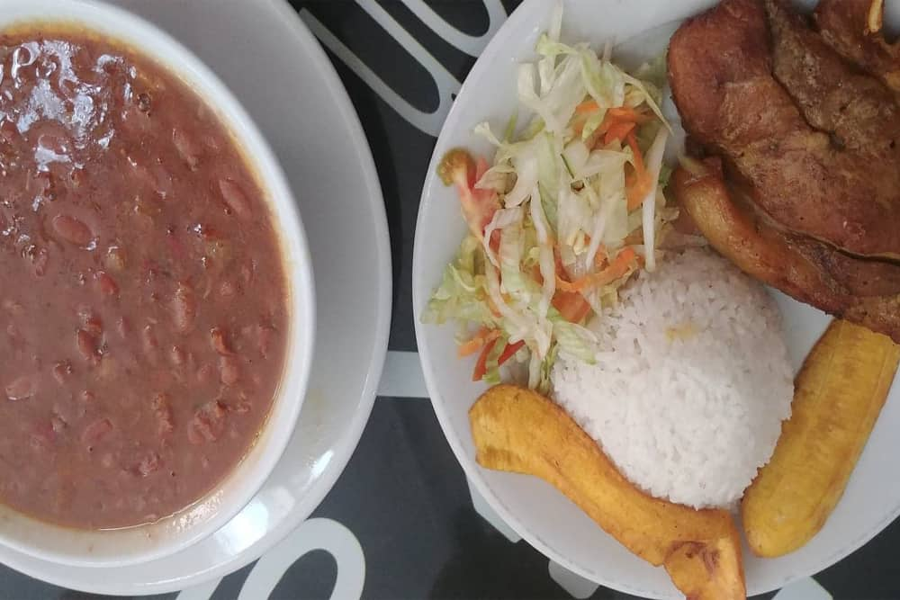 Bowl of beans and a plate with pork, rice, plantains and salad