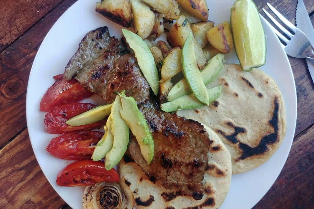 Plate with grilled beef, tortillas, tomatoes and avocado