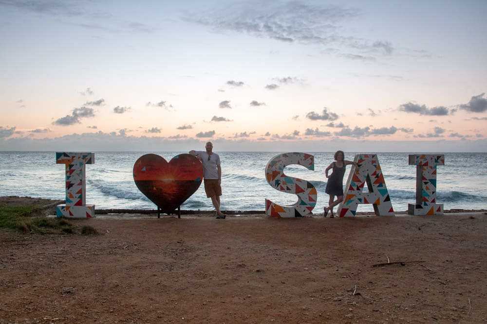 "Two people beside a sign of letters reading 'I ""heart symbol"" S A I'"