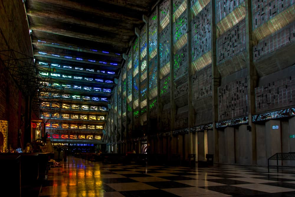 Dark building with different coloured glass letting colourful light inside.