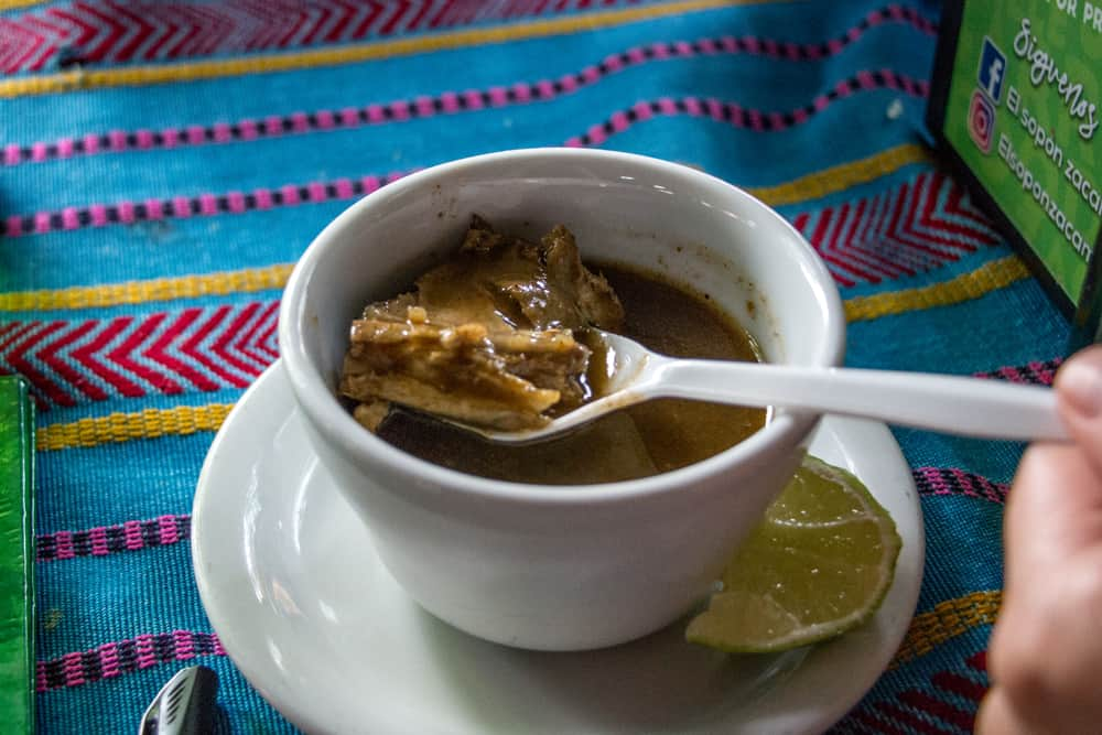 Bowl of soup with a spoon holding some iguana meat