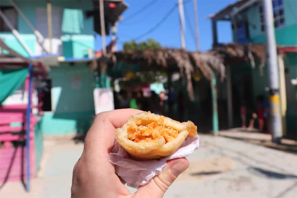 Hand holding an empanada witha green building in the background
