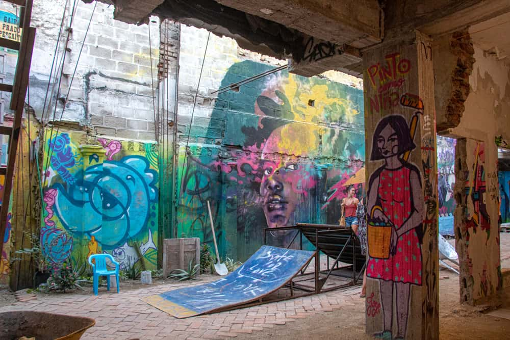 Abandoned building with colourful street art on the walls and a small skateboard ramp