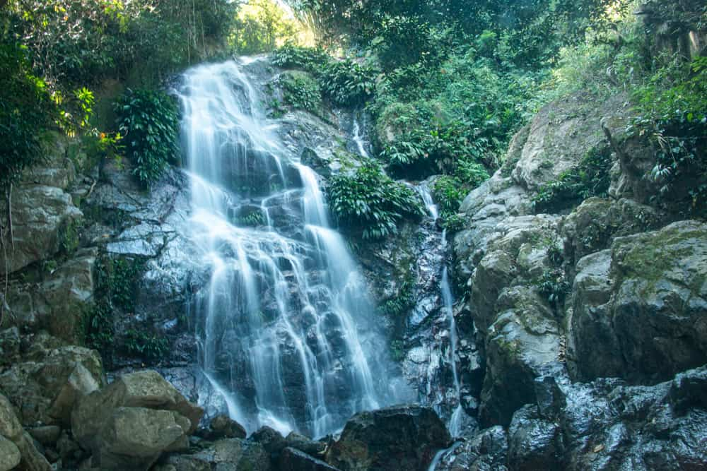 Waterfall against rocks with jungle in the background