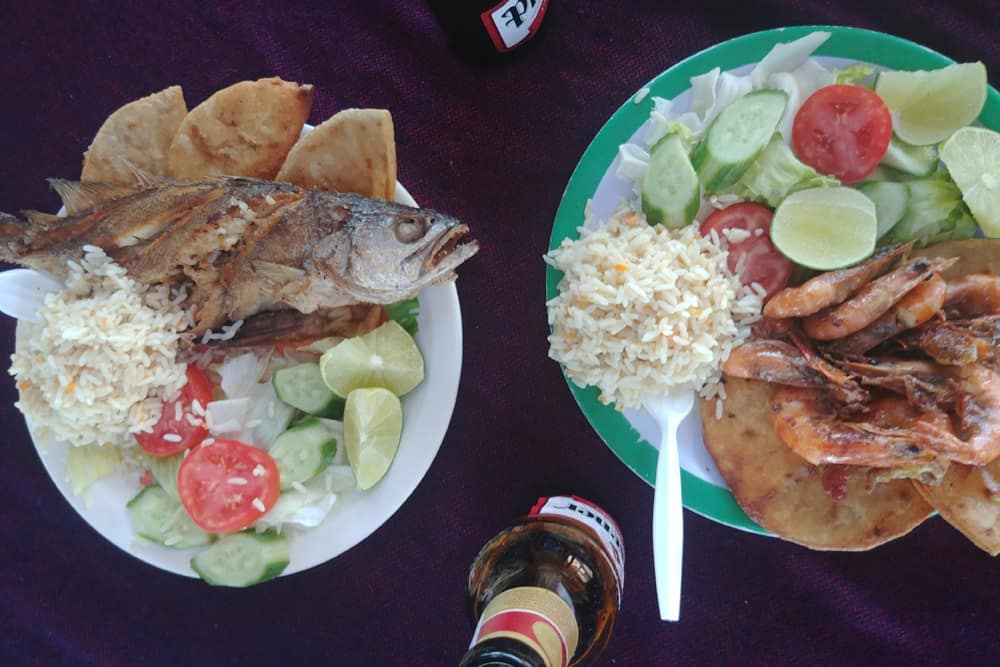 Two plates of food, one with prawns and one with fried whole fish