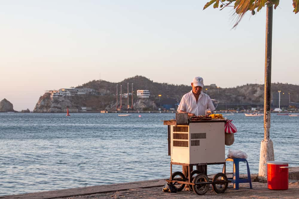 Man at a small cart grilling skewers of meat