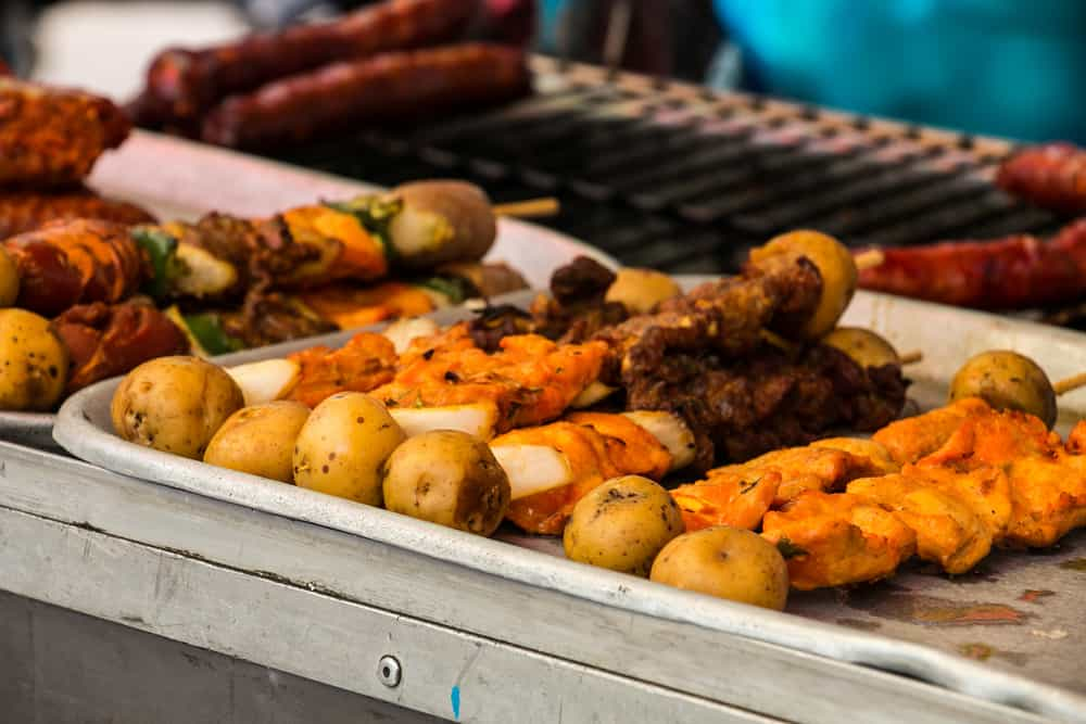 Skewers of meat and potato grilling. Eating street food is one of the best things to do in Santa Marta.