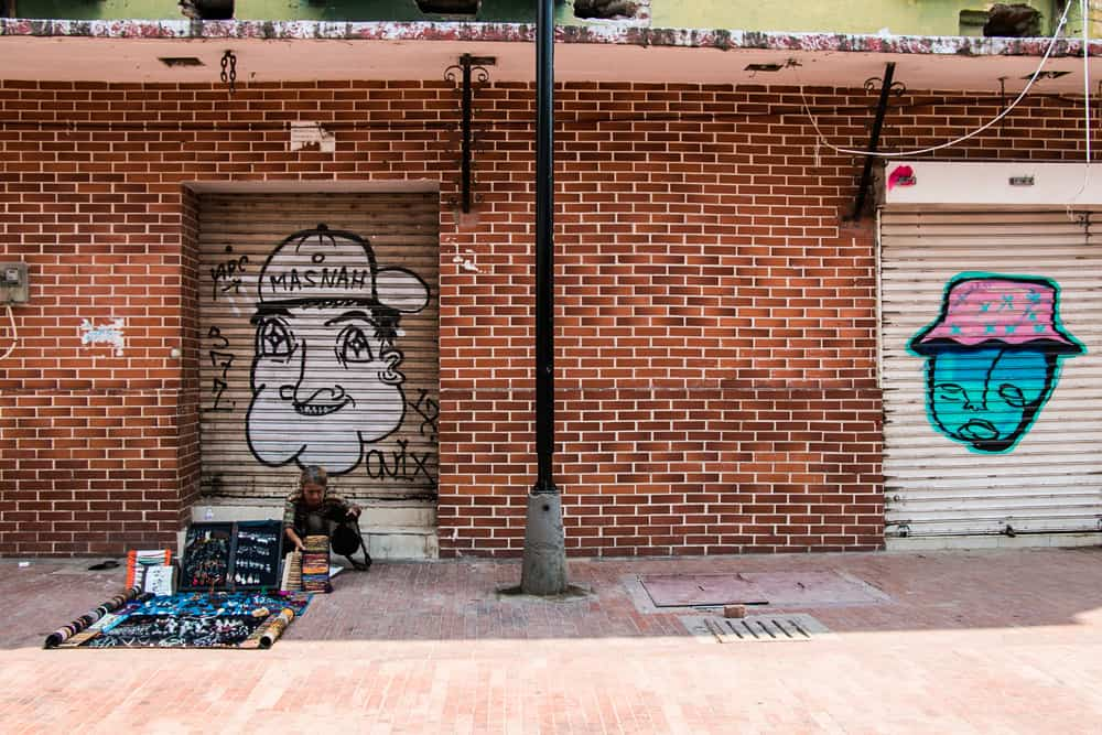 Brick wall with a person selling crafts on the street