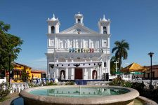 White colonial church behind a fountain in El Salvador