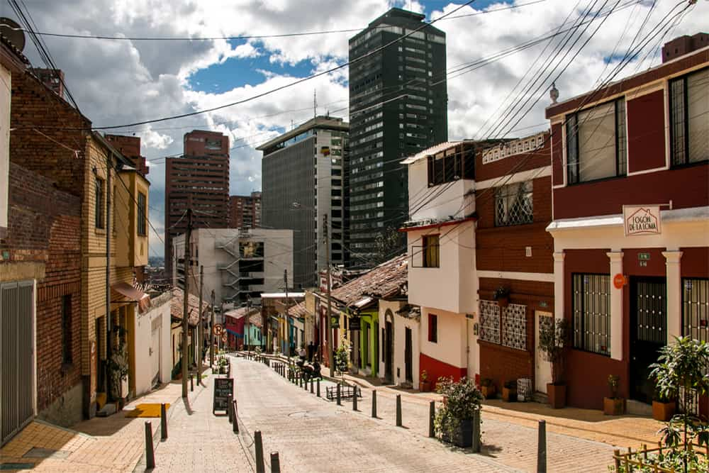 A bright street with colourful buildings. Skyscrapers of downtown Bogota in the back.