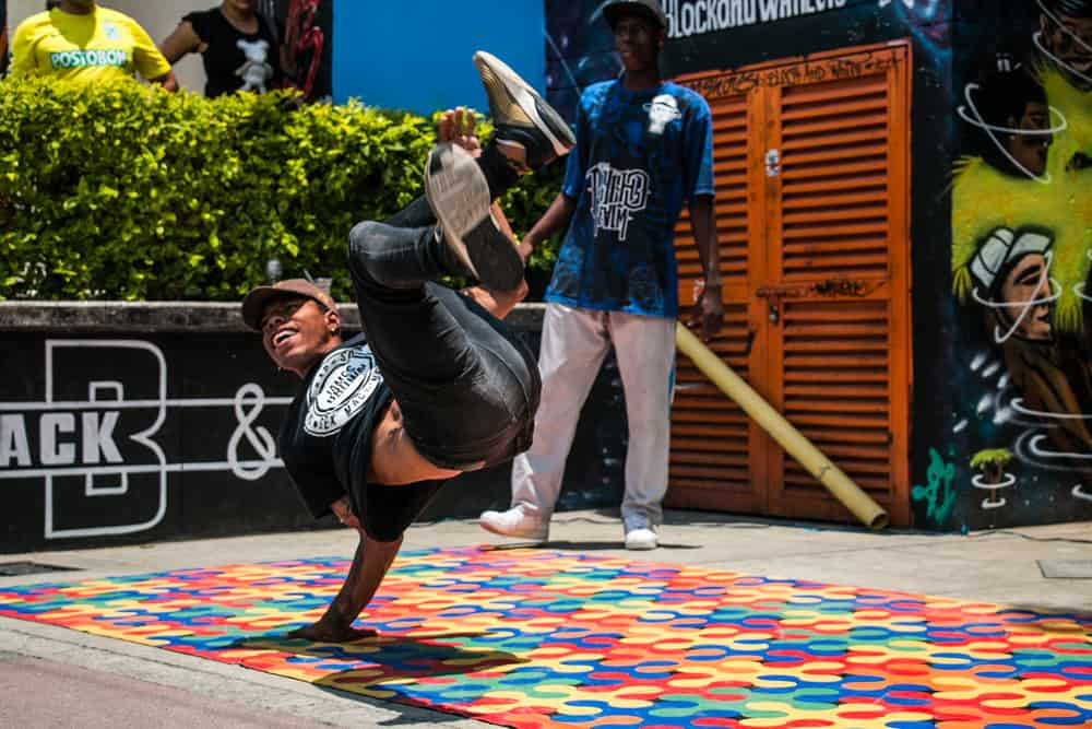 Breakdancer performing on a colourful painted ground