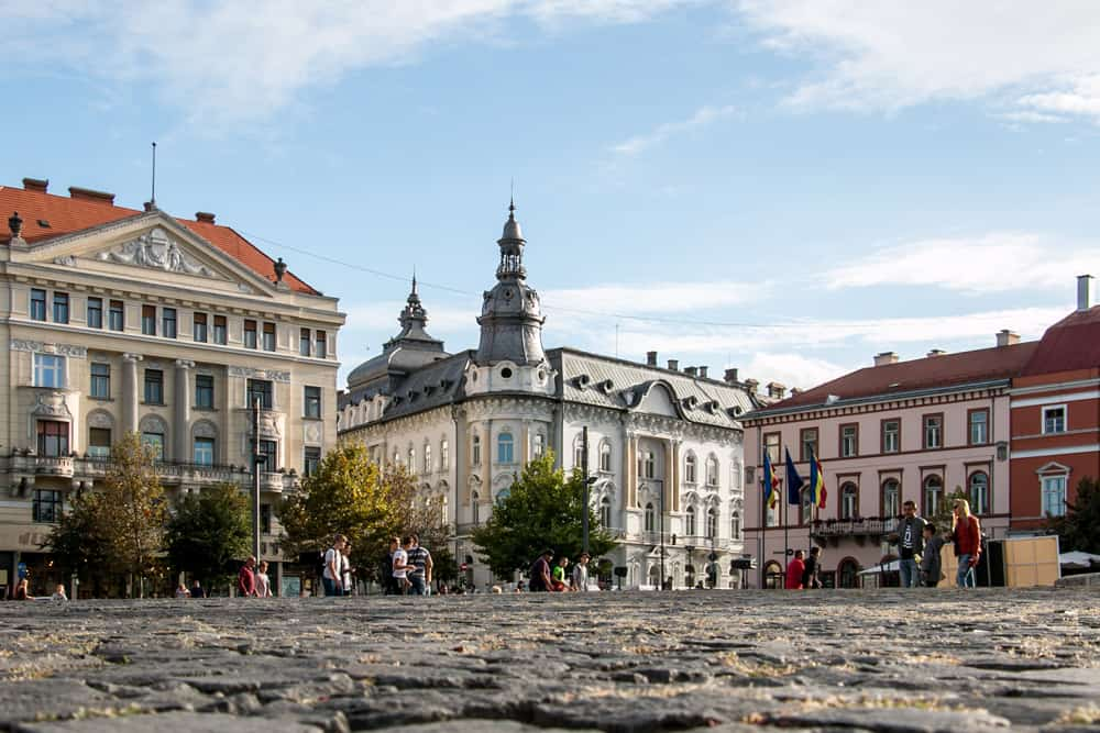 Union Square in Cluj. Cobblestones surrounded by colourful buildings.
