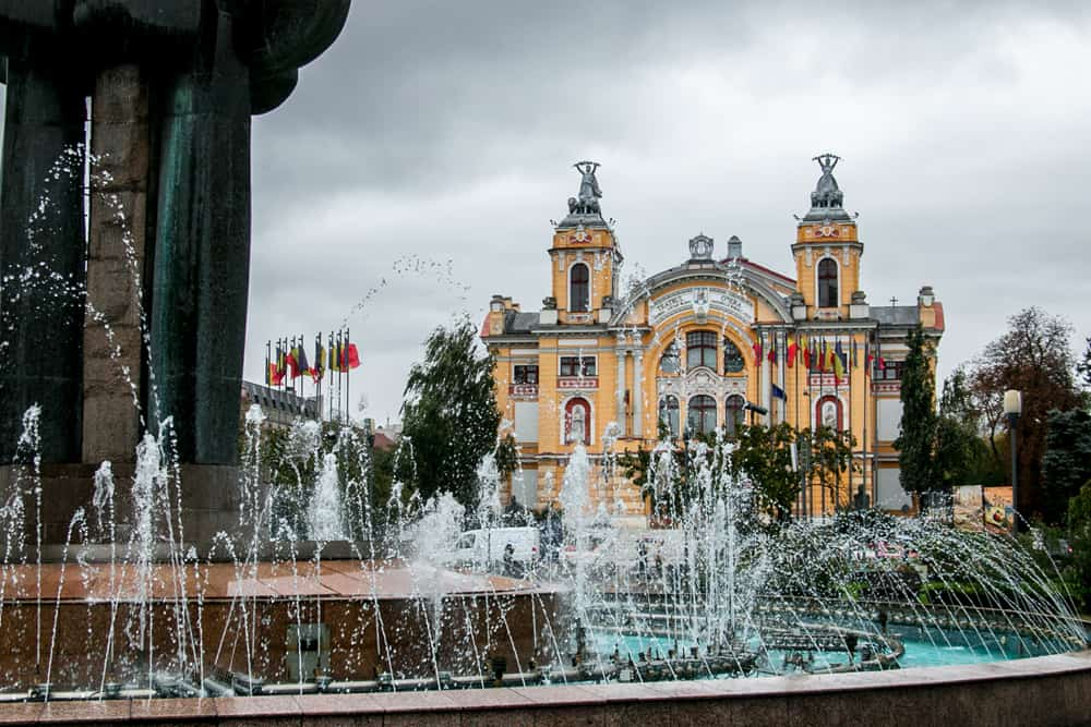 A statue and fountain with a bright orange building in the background