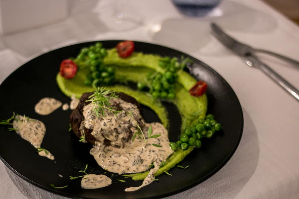 Black plate with a steak covered in a cream sauce. A green pea puree is spread around it.