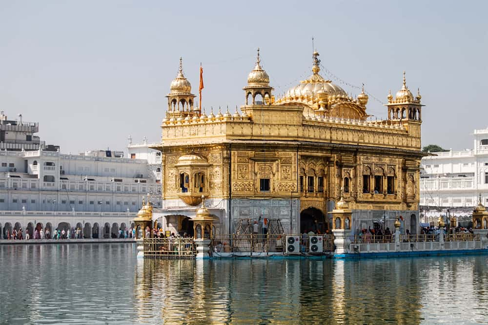 Gold covered building surrounded with a pool of water