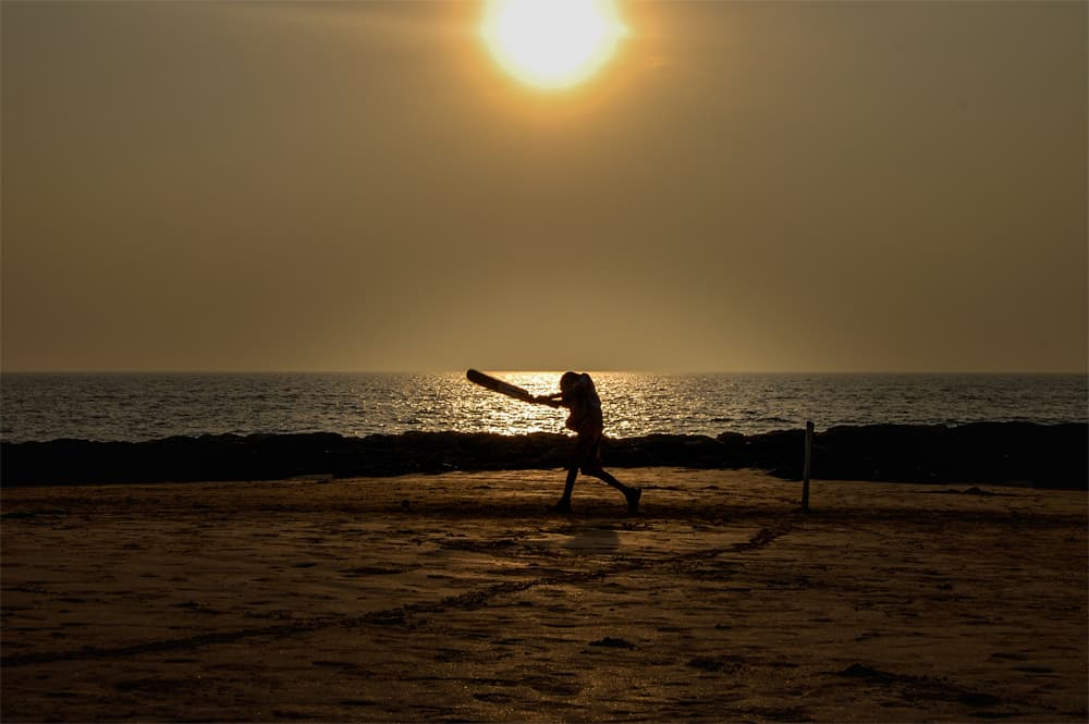 Silhouette of boy playing cricket on the beach