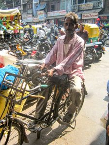 Man sits on a bike converted into a knife sharpener