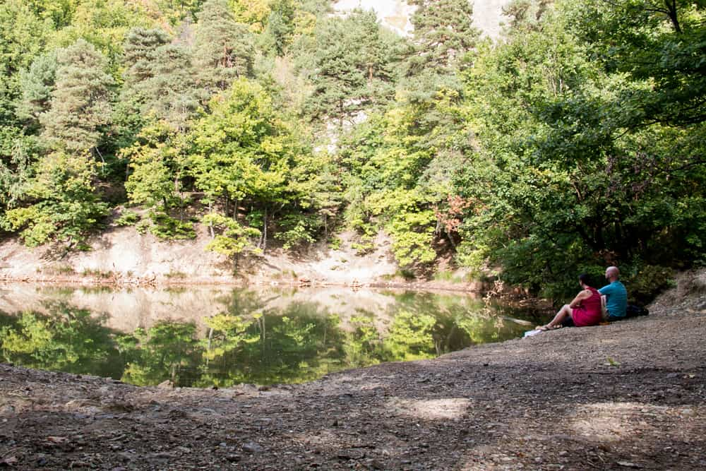 Two people sit beside a pond