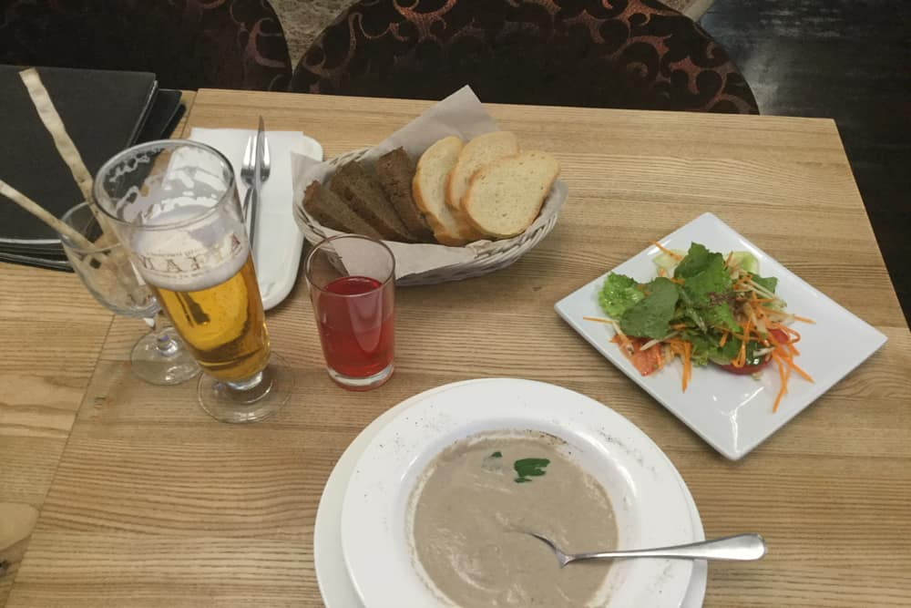Two glasses, one beer one red juice, a plate of salad and a bowl of soup
