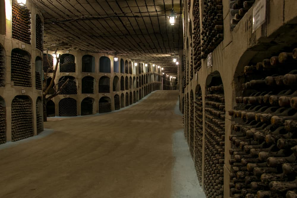 Underground tunnel with wine bottles in wall holes