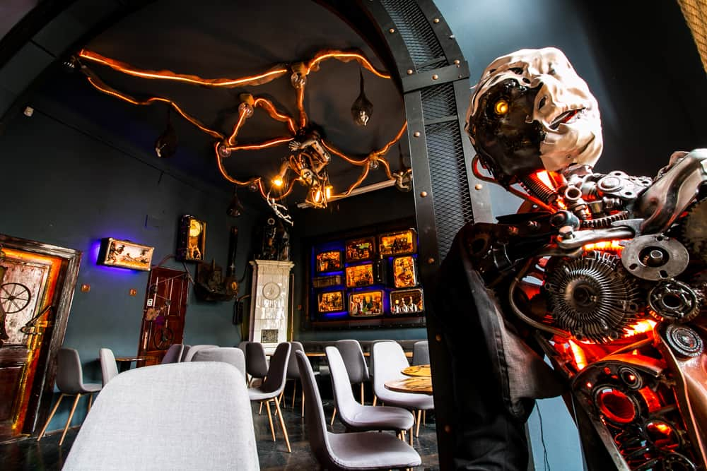 A cyborg manequin is sitting in a chair with colourful art behind him.