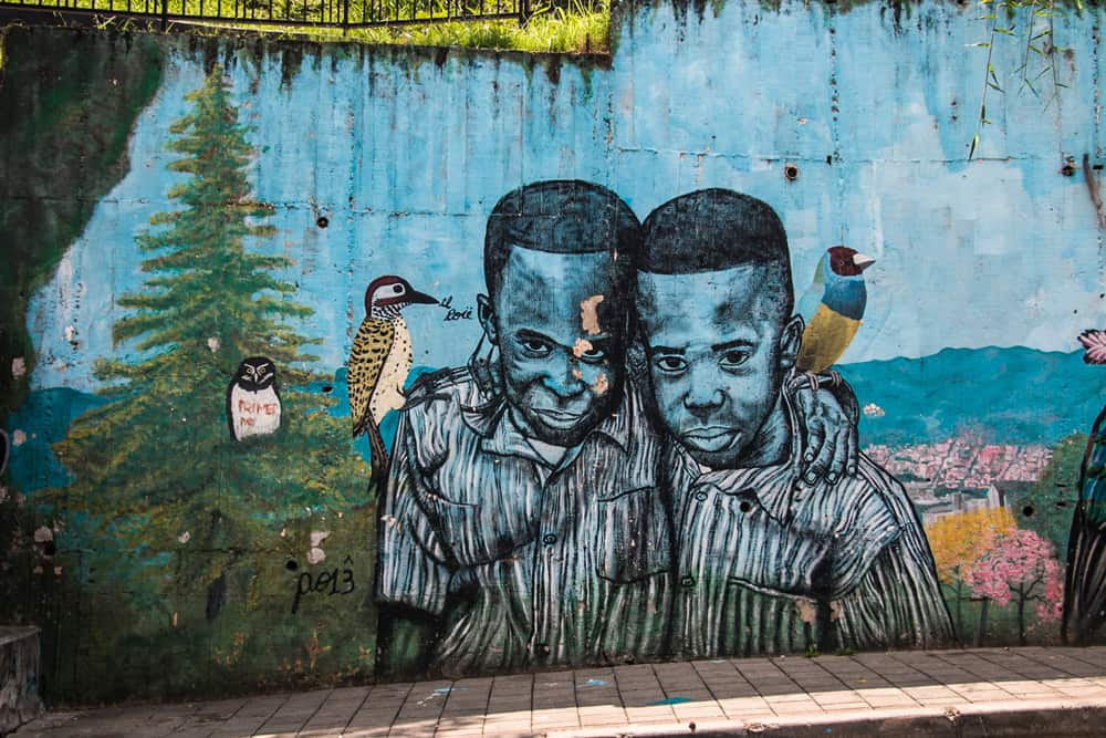 Blue wall with art depicting two boys hugging