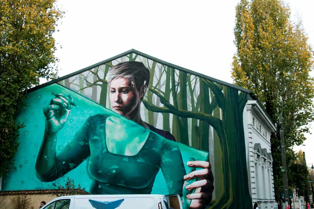 Green street art of a girl on a wall