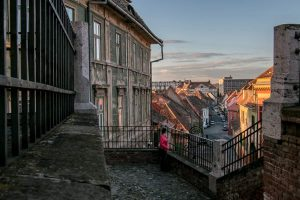 Sibiu Romania: Girl standing near a rooftop at sunset