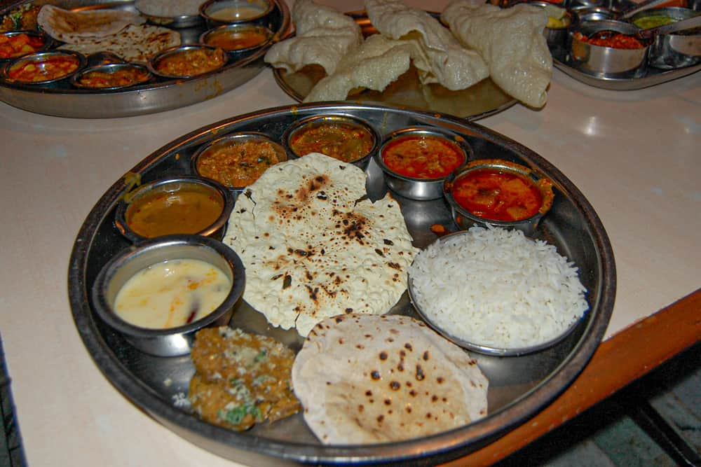 Silver platter with many different sauces on it and a pile of rice