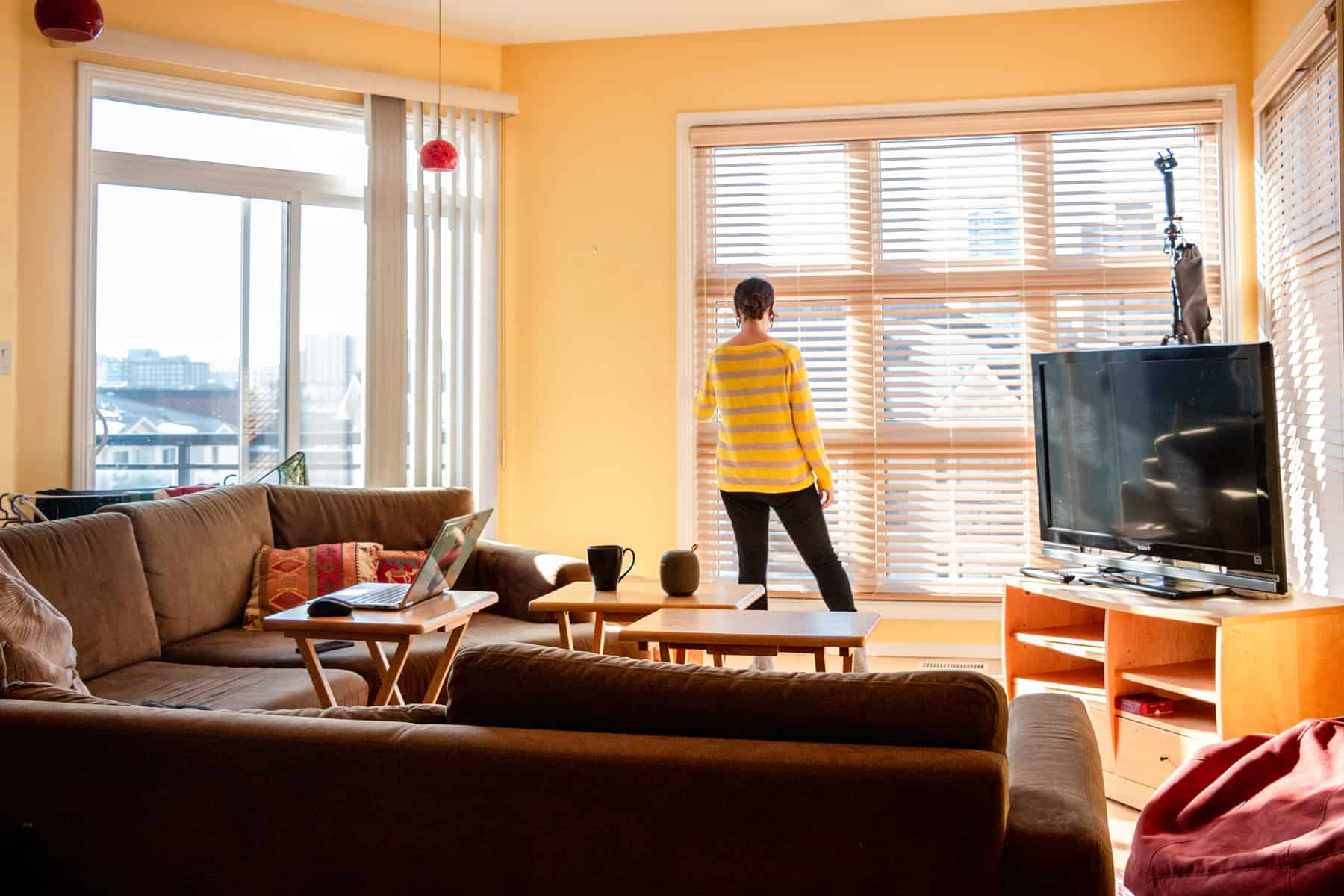 Woman looking out a window in a living room