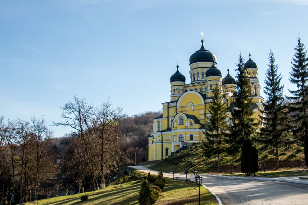 Intricate yellow church on a hill surrounded by trees
