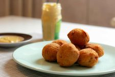 Deep fried round snacks on a plate with a jar of mustard in the background.