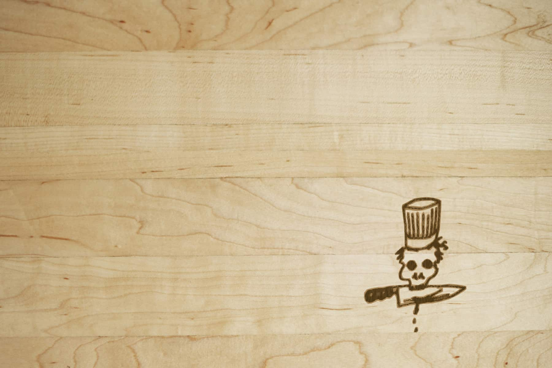 Wooden cutting board with a skull in a chef hat burned into it.