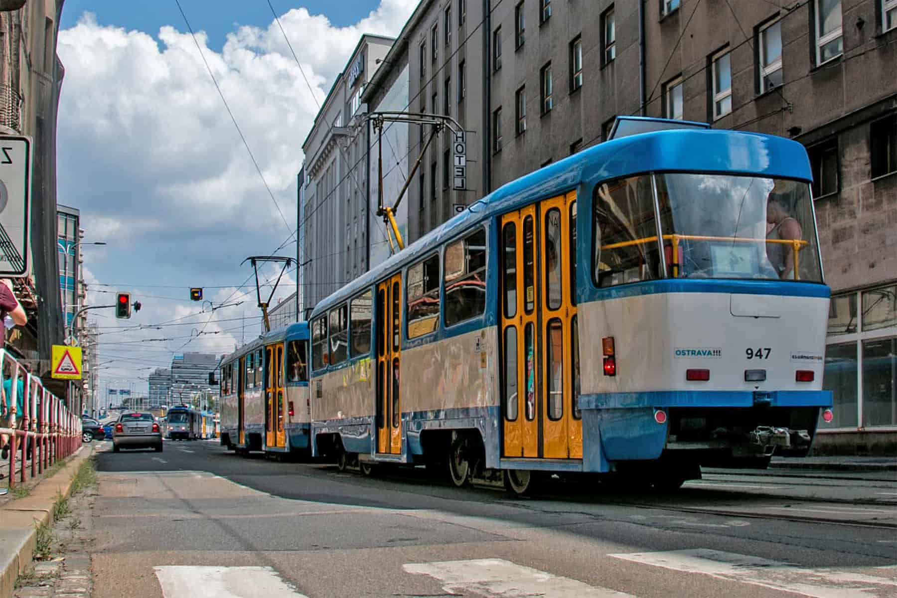 Blue yellow and white tram on a European road