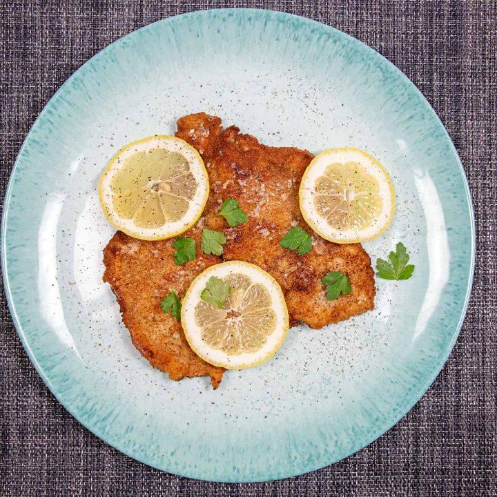 Wiener schnitzel with lemon on a blue plate
