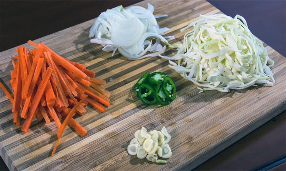 Carrots, cabbage, onions, garlic and jalapeno on a cutting board.