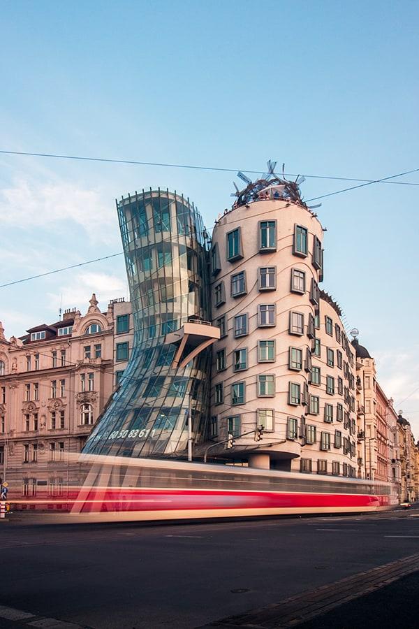 Tram passing two strange buildings