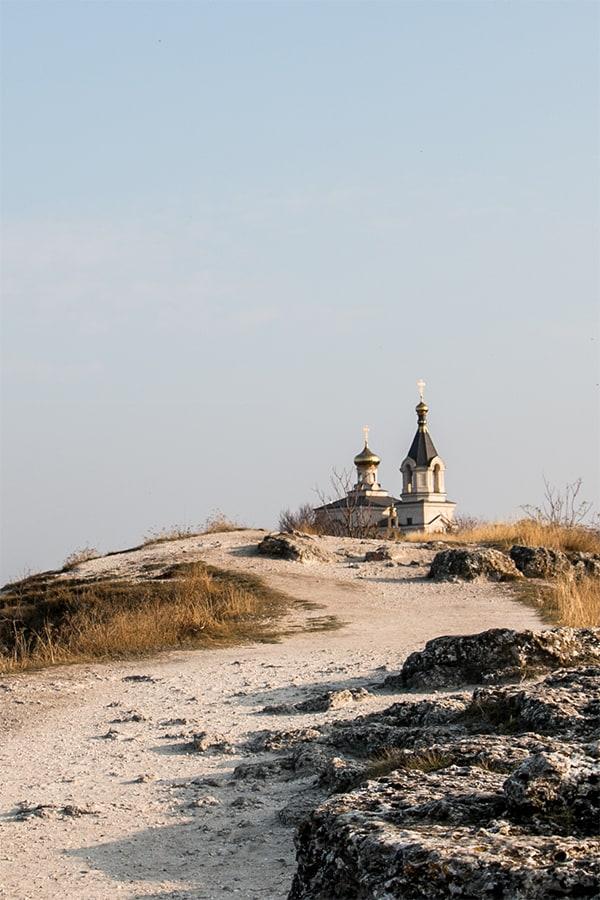 Dirt path towards a church on a hill.