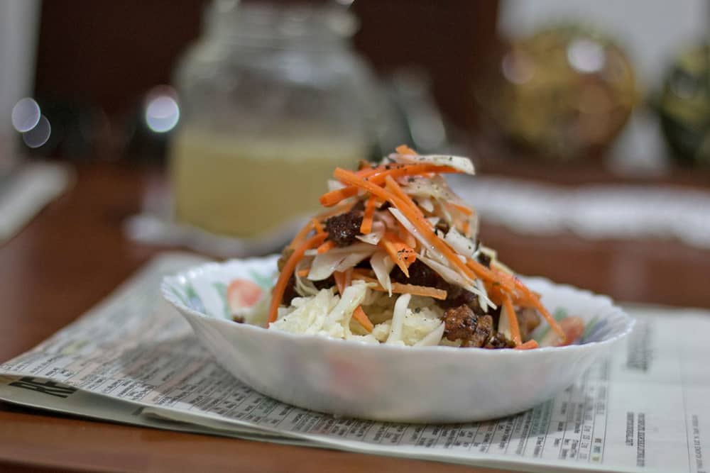White bowl with yuca, pork and carrot slaw